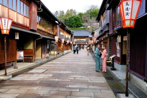 two women in kimonos posing in a street lined with traditional buildings in kanazawa japan