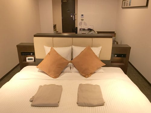 bed in hotel room with seating area in background