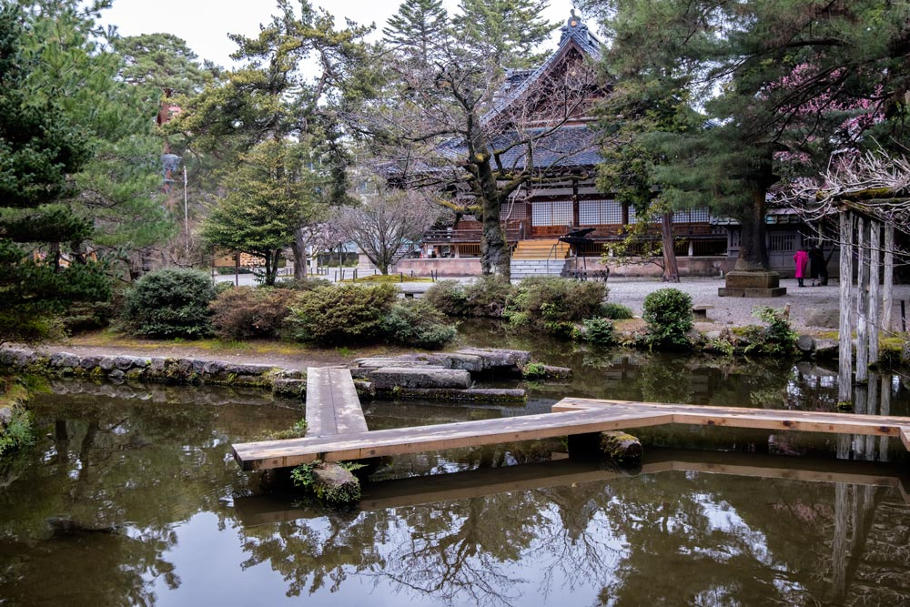 japanese shrine main building with traditional garden with pond in foreground
