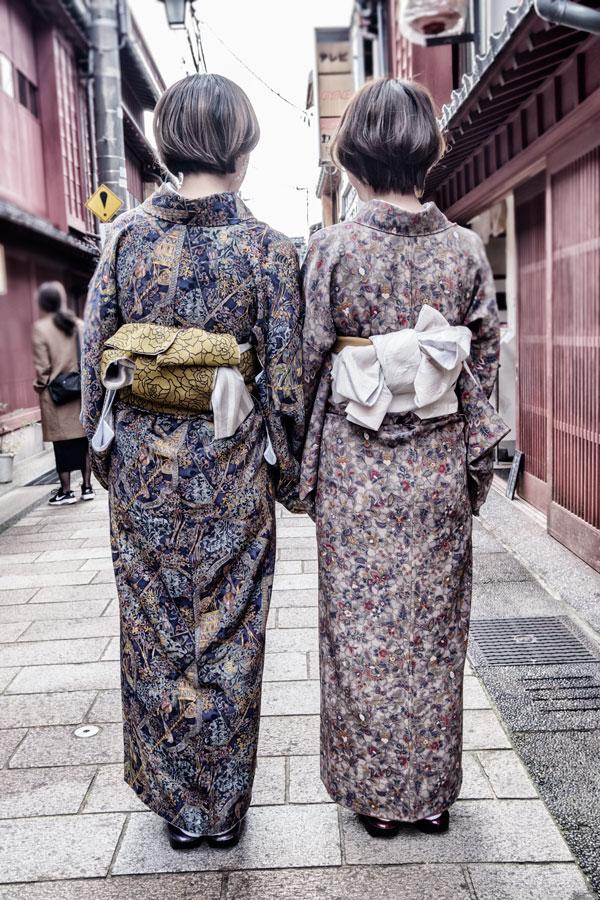 the back of two women dressed in kimonos walking along street