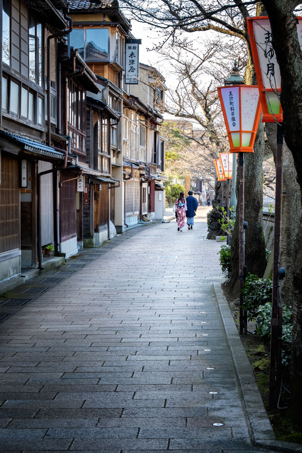 couple in traditional dress walking alonf street in kanazawa lined with traditional buildings