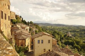 golden stone walls of tuscany hill village overlooking green rolling landscape
