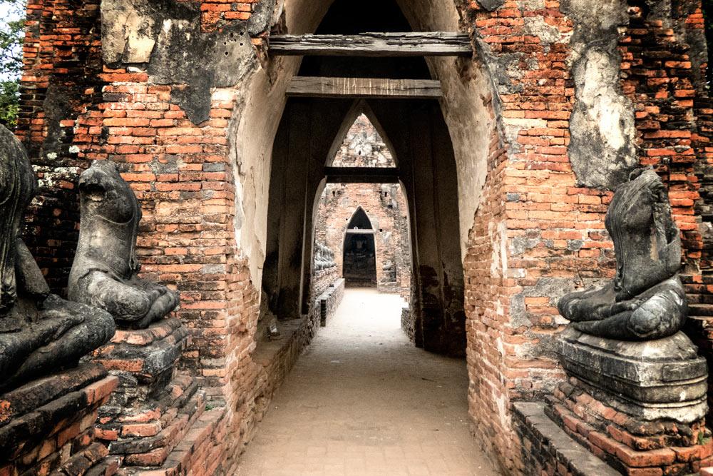 headless buddhas lining passageway in temple in ayutthaya