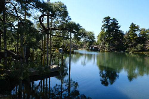 still pond with reflections of trees and tea house at kenroku-en one of the best things to see in kanazawa japan