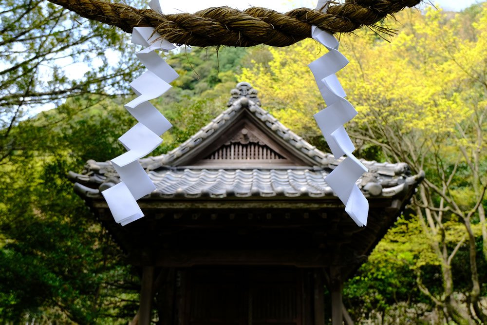 prayers tied to rope in front of japanese shrine