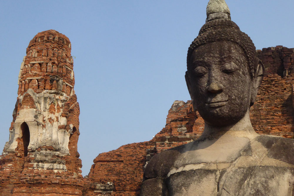 head of buddha with ruined temple buildings in background