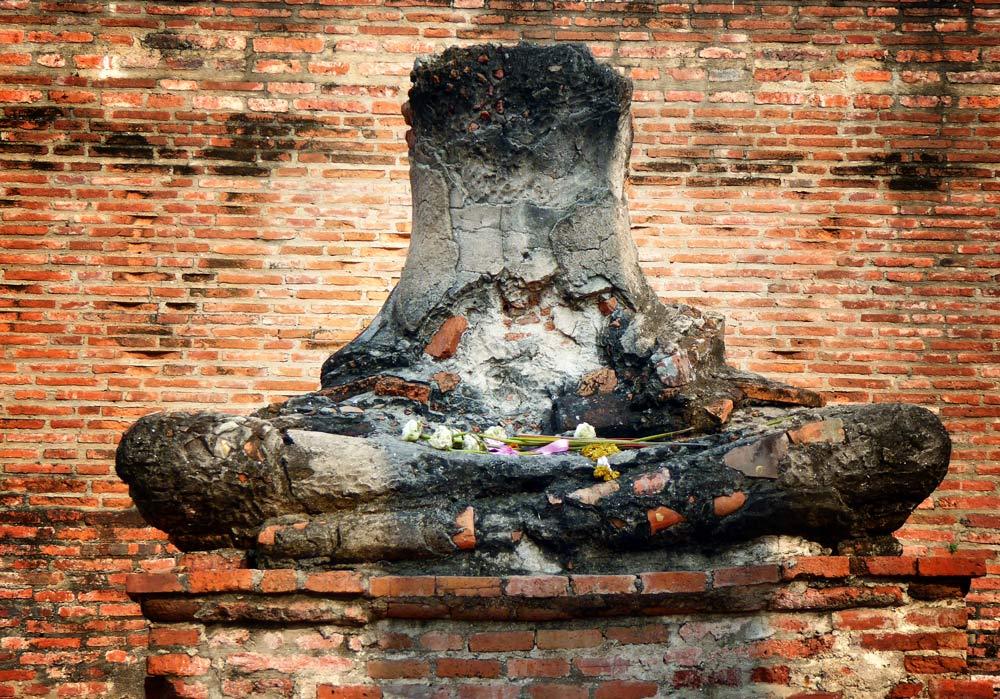 bottom half of stone buddha statues strewn with flowers