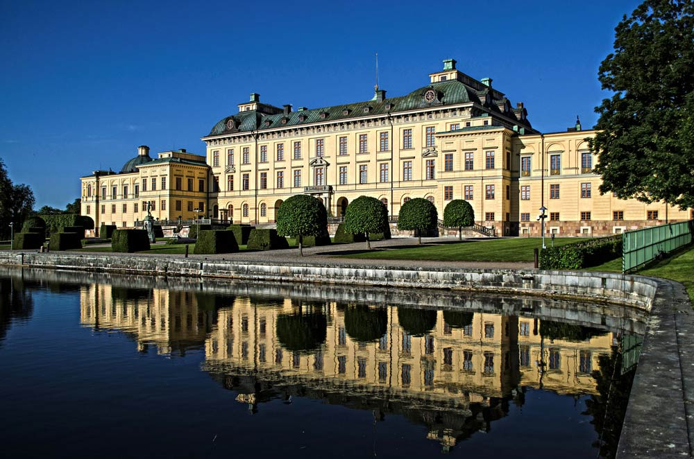 cream facade of drottningholm palace reflected in still blue water