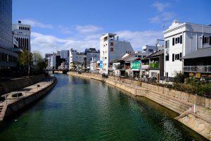 buildings lining the riverfront in fukuoka japan