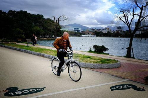 man riding bike along lakeside promenade at ohori gardens fukuoka