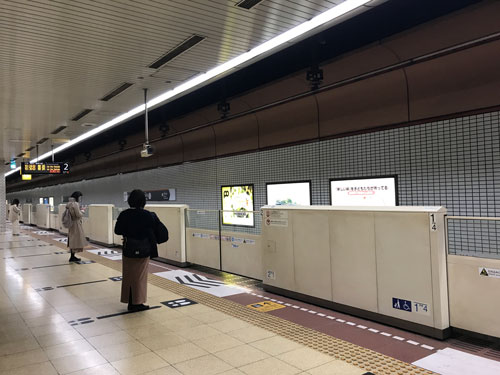 people waiting on platform for subway train in fukuoka japan