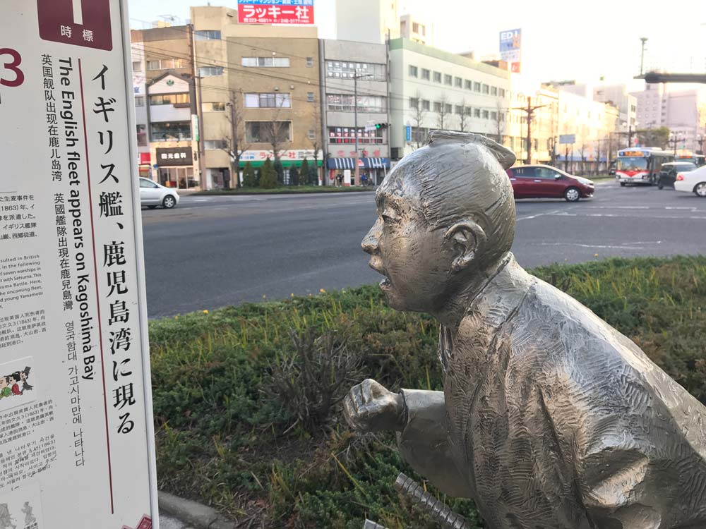 bronze sculpture of japanese man looking at information board