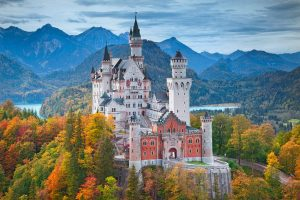 fairytale castle that is a beautiful european palace with a mountain and lake backdrop