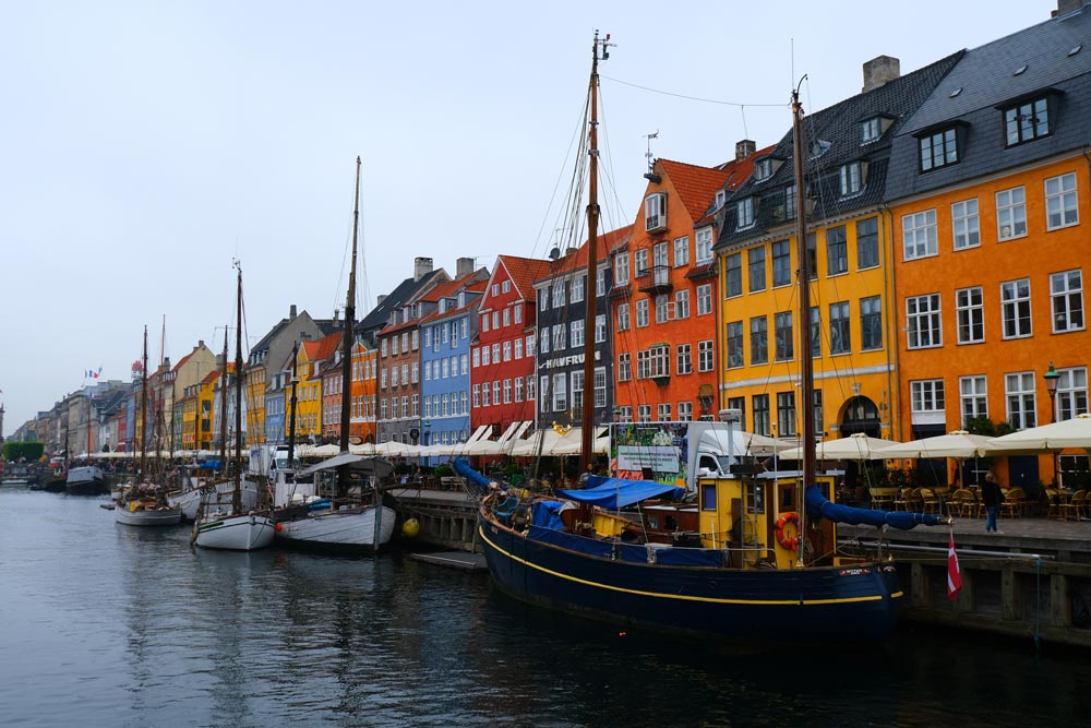 brightly coloured housesd along the waterfront with boats in nyhavn