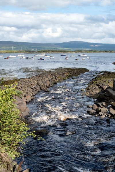waves in harbour with hills and boats in background in tobermory mull scotland