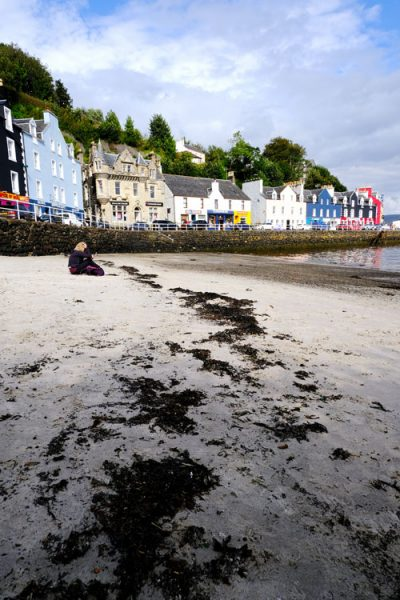 woman sitting on sand in tobermory with brightly coloured houses in background