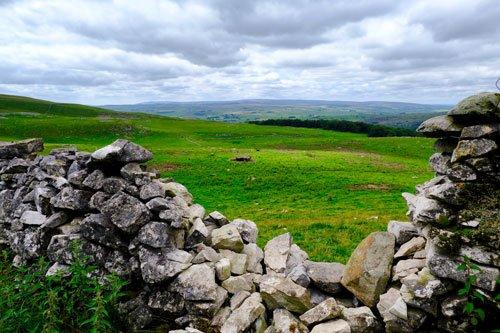 green fields through gap in dry stone wall