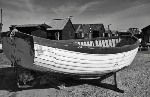 wooden boat in front of wooden harbour huts