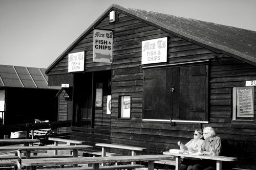 man and woman sitting at table outside wooden fish and chip shop