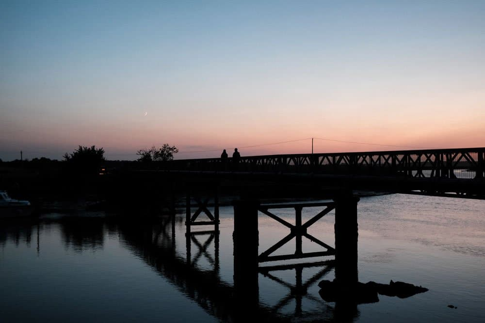 two people walking over a bridge at sunset