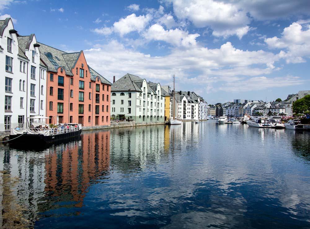 pastel colored buildings reflected in water in Alesund-Norway
