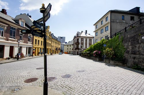 cobbled street with signpost and pastel colored buildings