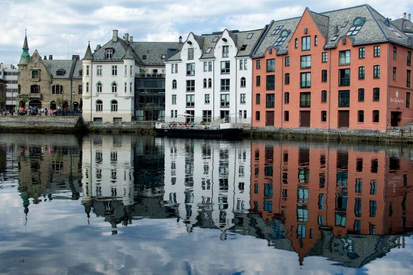 brightly colored buildings reflected in water of harbour in the art nouveau town of alesund norway