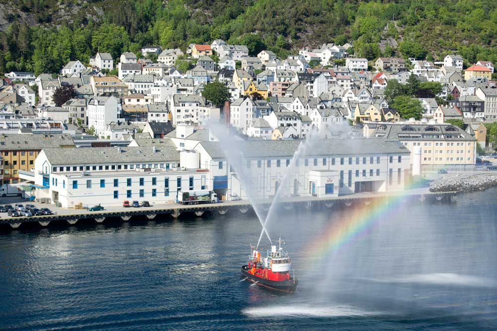 boat in pretty harbour of alesund with rainbow colours in water spray
