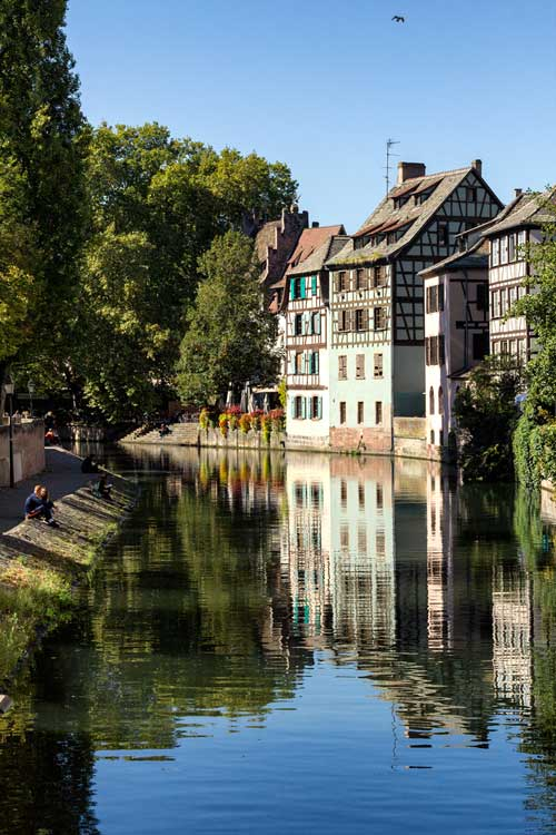 two people sitting on bank of pretty canal in strasbourg france