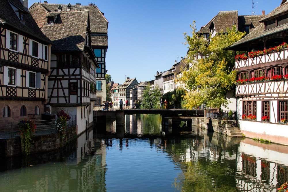 people on bridge between half timbered buildings in strasbourg france