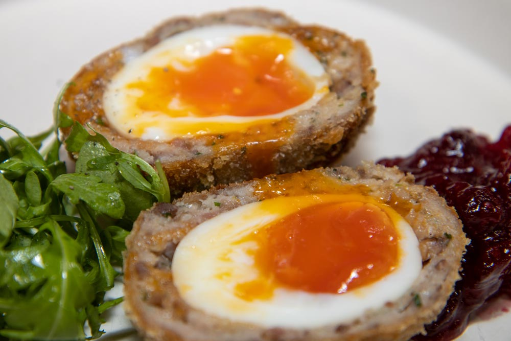 two scotch eggs on a plate