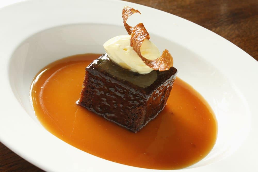 sticky toffee pudding in white bowl topped with ice cream