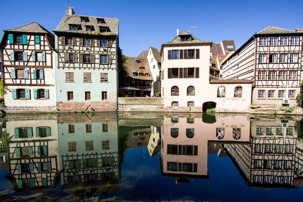 half timbered buildings reflected in canal seen in one day in strasbourg free walking tour