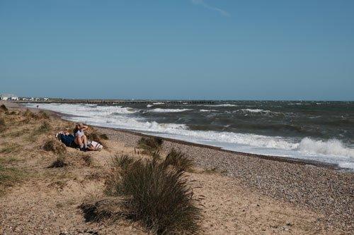 2 people sitting on walberswick beach