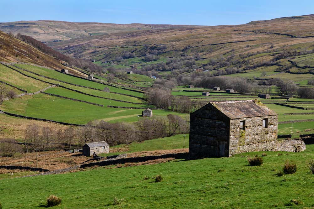rolling fields and stone barn in valley