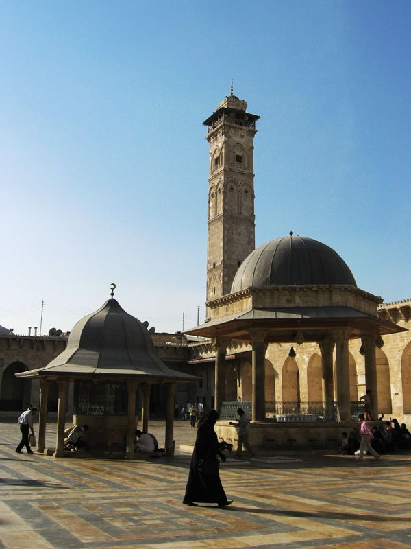 woman walking across the courtyard of a mosque