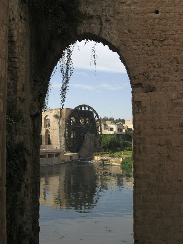 view of a water wheel through an arch