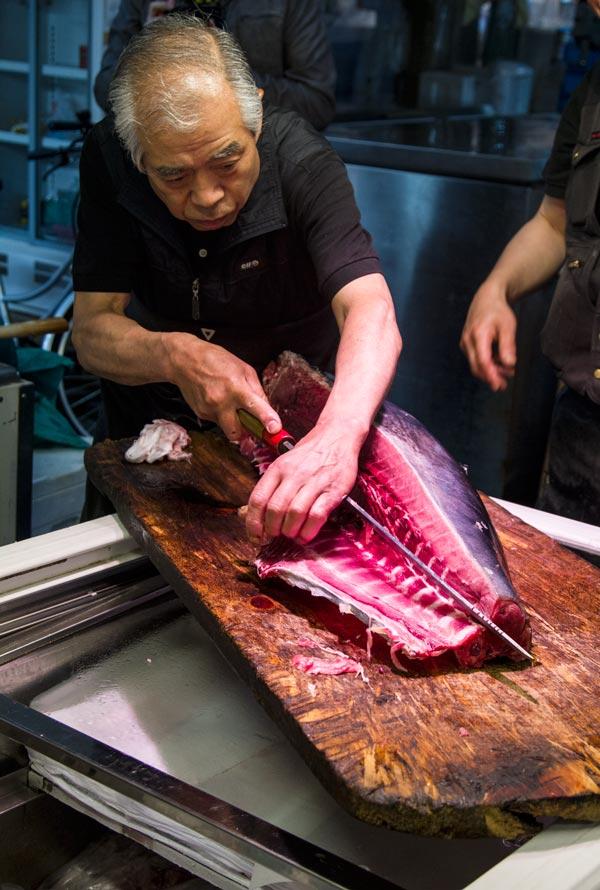 japanese man gutting a tuna fish