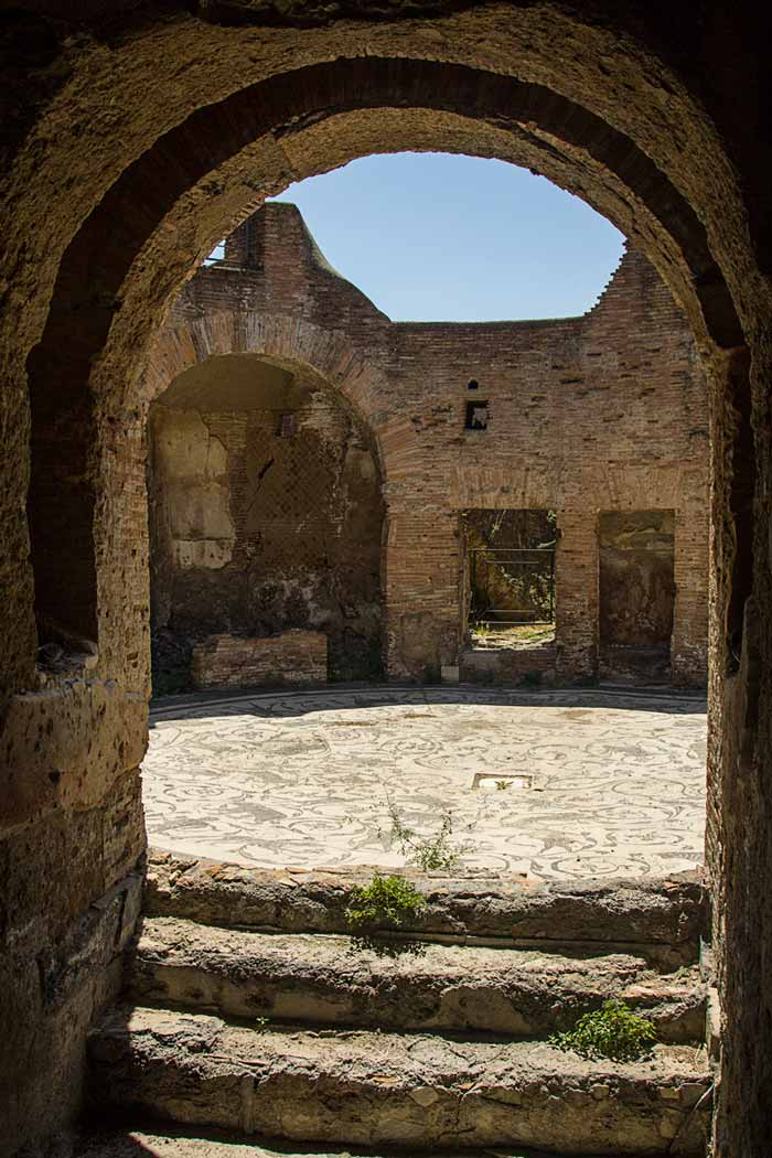 looking through stone arch to courtyard with mosaic floor at ostia antica rome