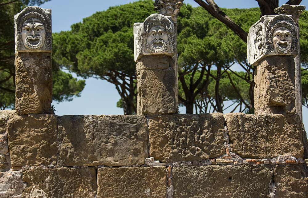 stone heads on top of columns at the ancient roman site of ostia antica visited as a day trip from rome