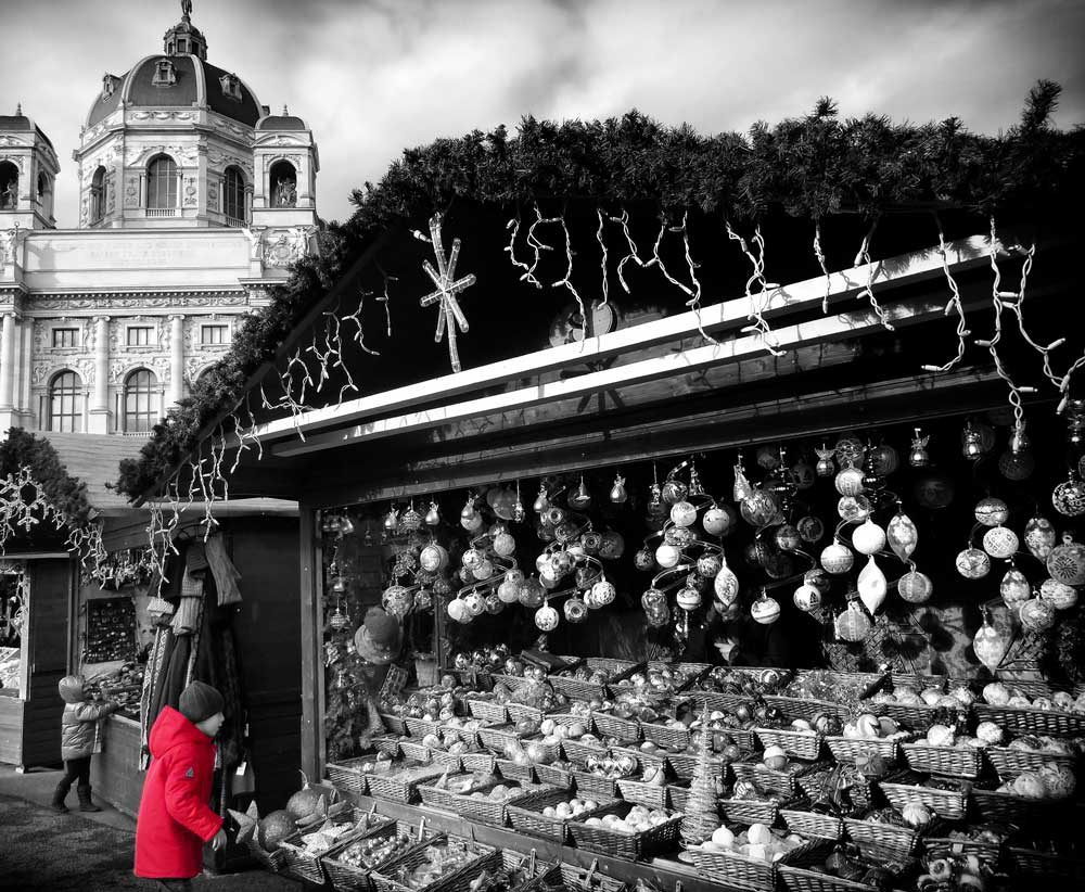 child in red coat at stall in xmas market