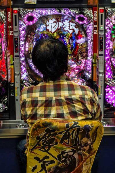 man sitting in front of a pachinko machine