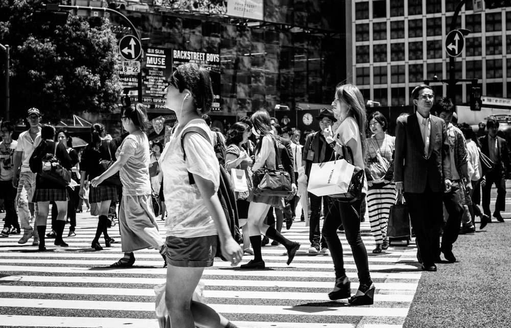 people walking across a busy pedestrian crossing