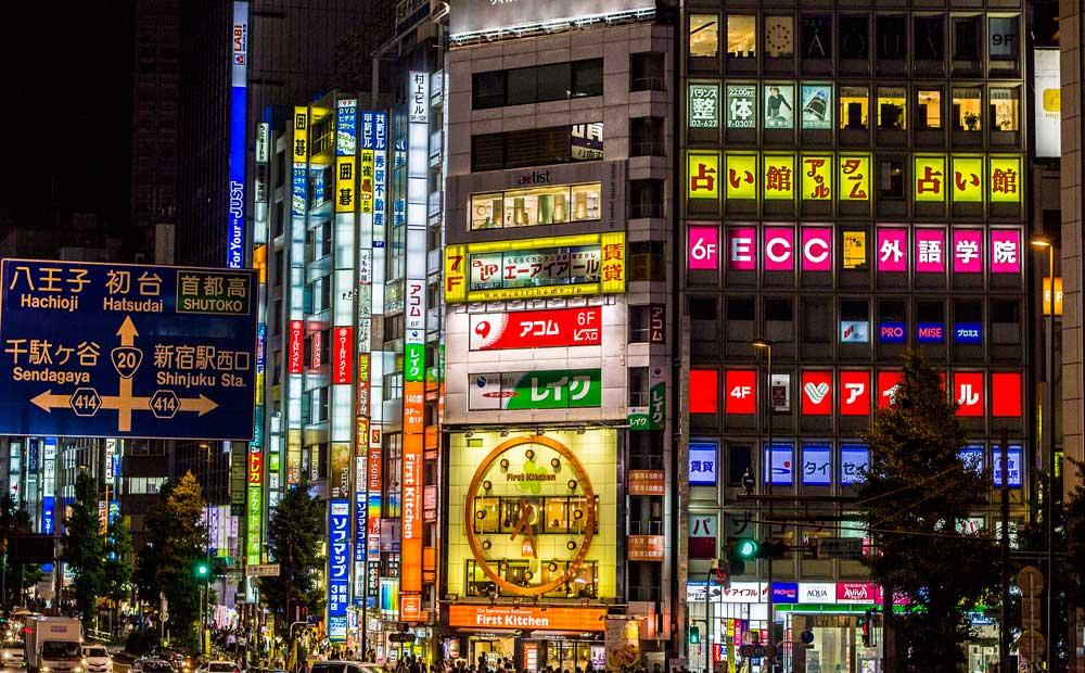 street scene in tokyo at night with neon lights