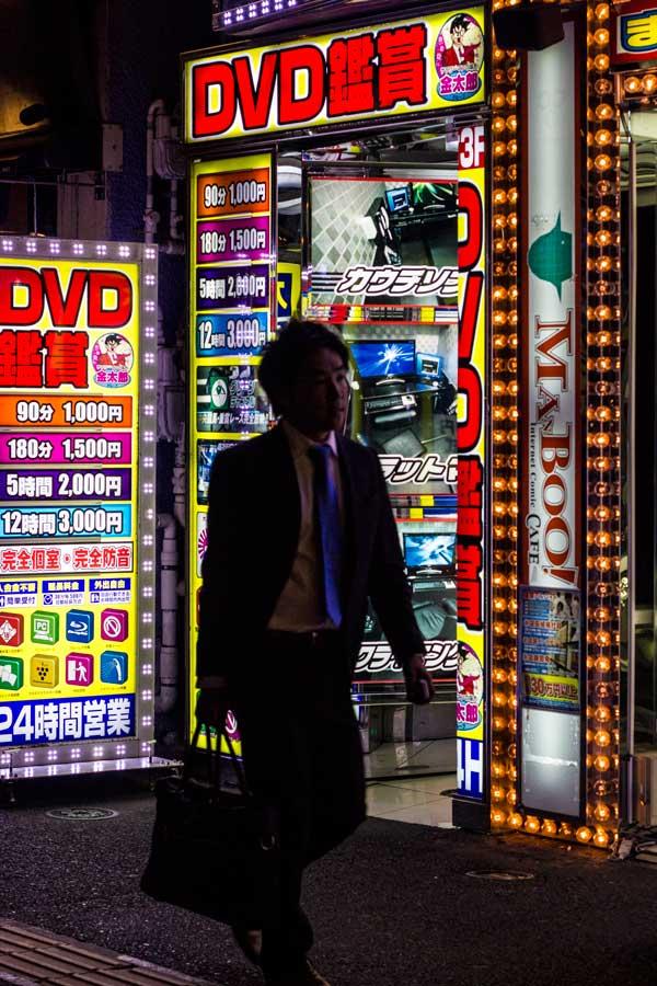 business man walking in front of a neon lit window