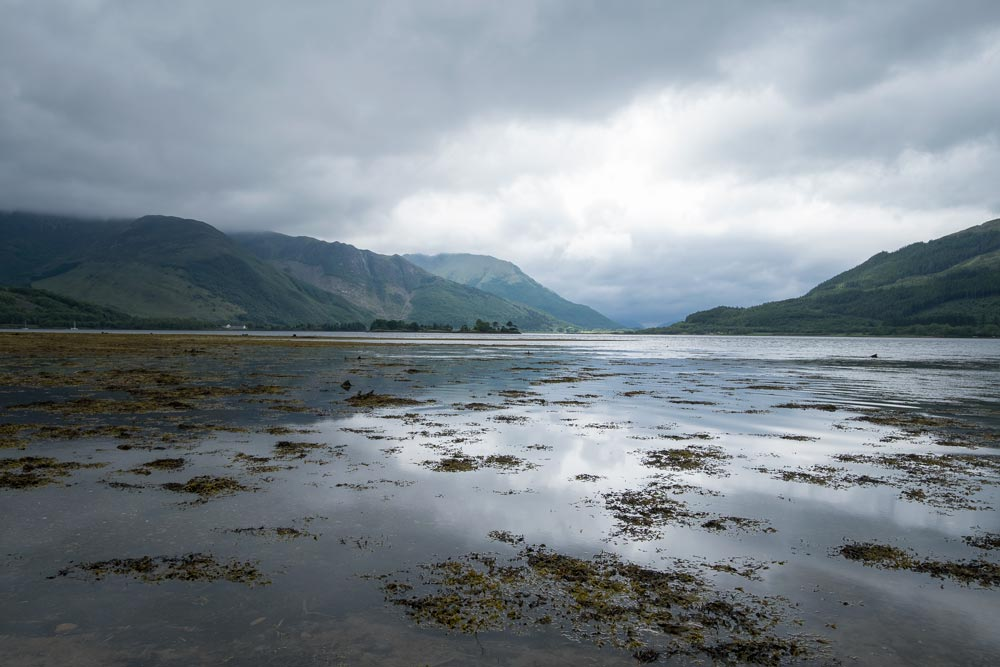 Still waters of loch in glen coe scotland with reflection of mountains