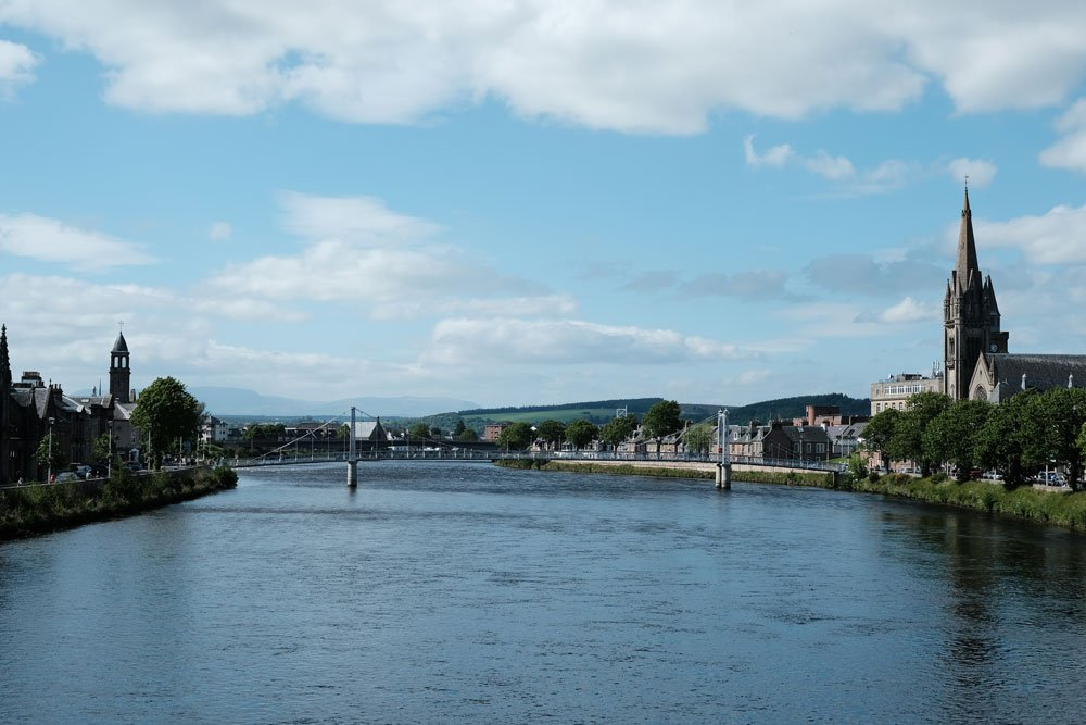 wide river in inverness in scotland with bridge and lined by buuildings