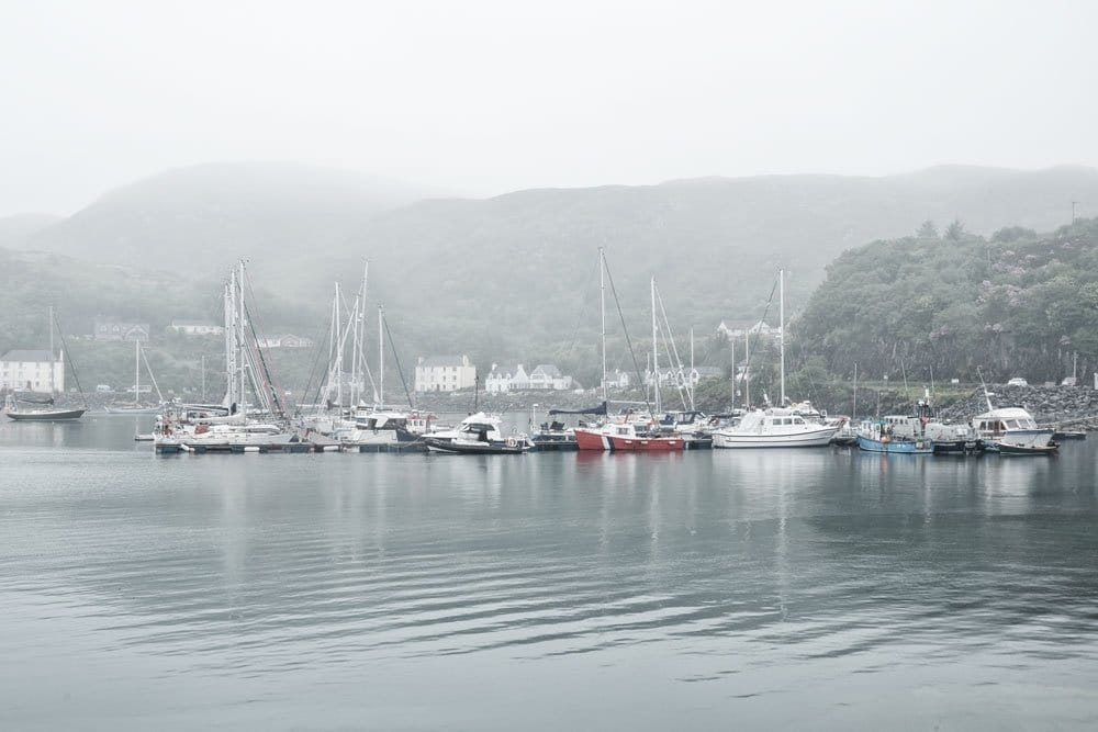 boats anchored in the misty harbour of mallaig scotland