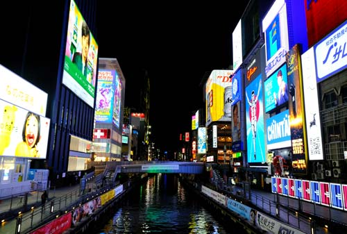 neon signs along the banks of a canal in osaka japan
