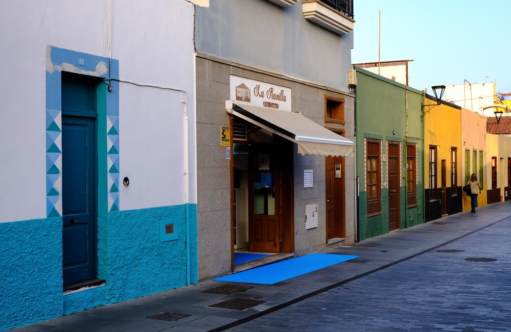 street with multicoloured buildings and woman walking past in puerto de la cruz tenerife